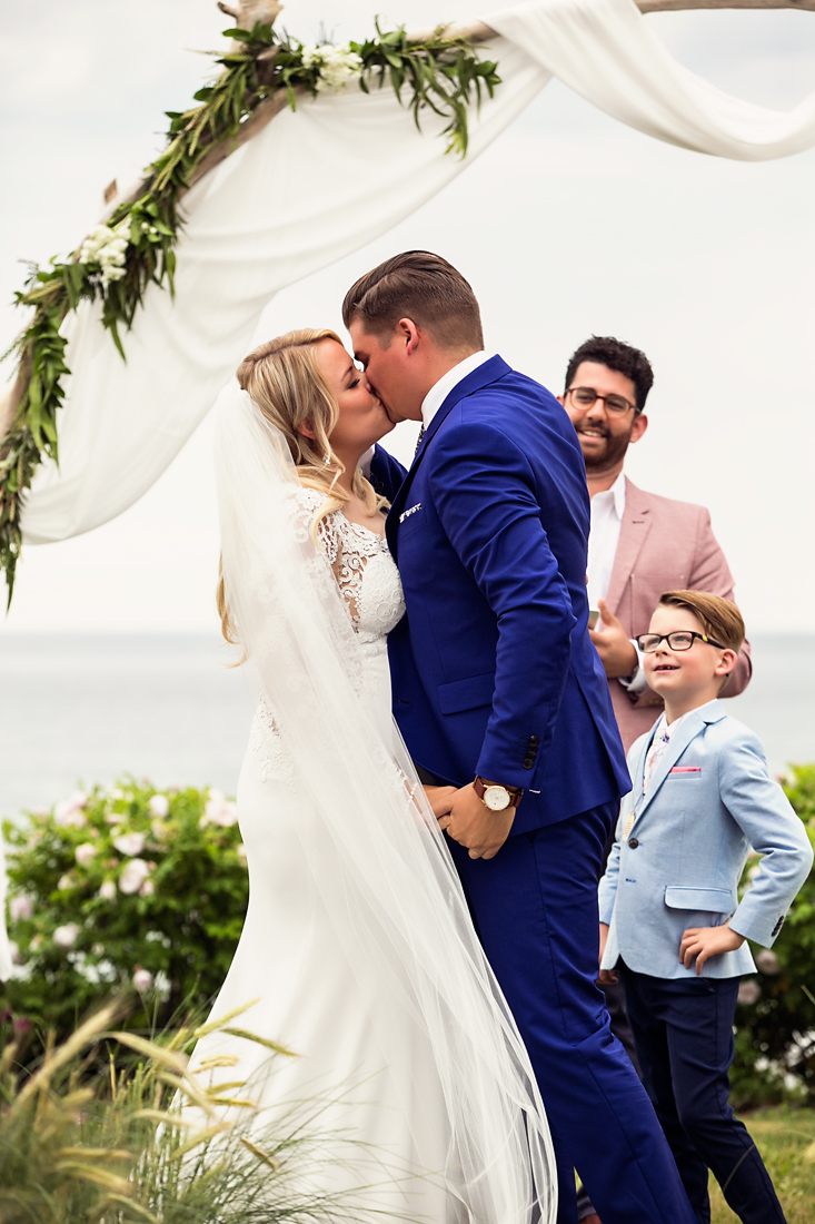 bride and groom kiss during rustic outdoor wedding ceremony at white point beach resort