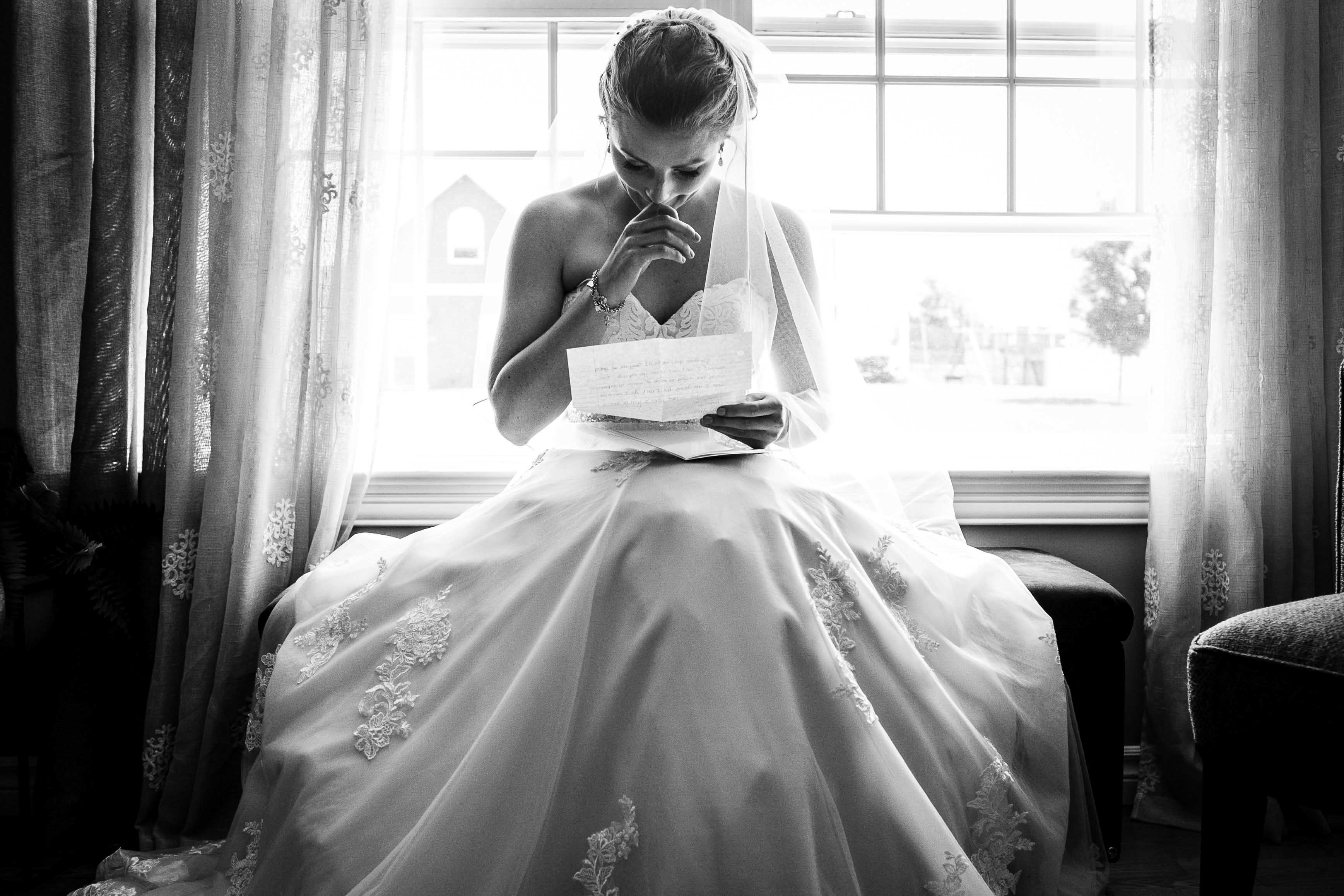 bride in embroidery wedding dress reading letter from groom emotional getting ready