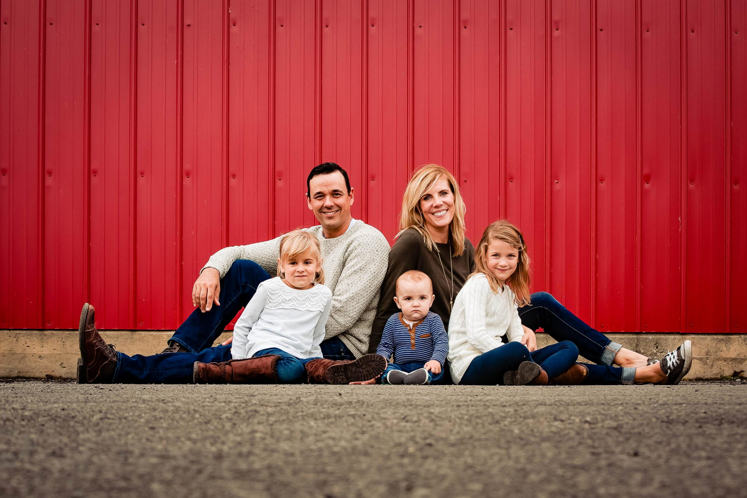 photo of a family sitting in front of a red wall