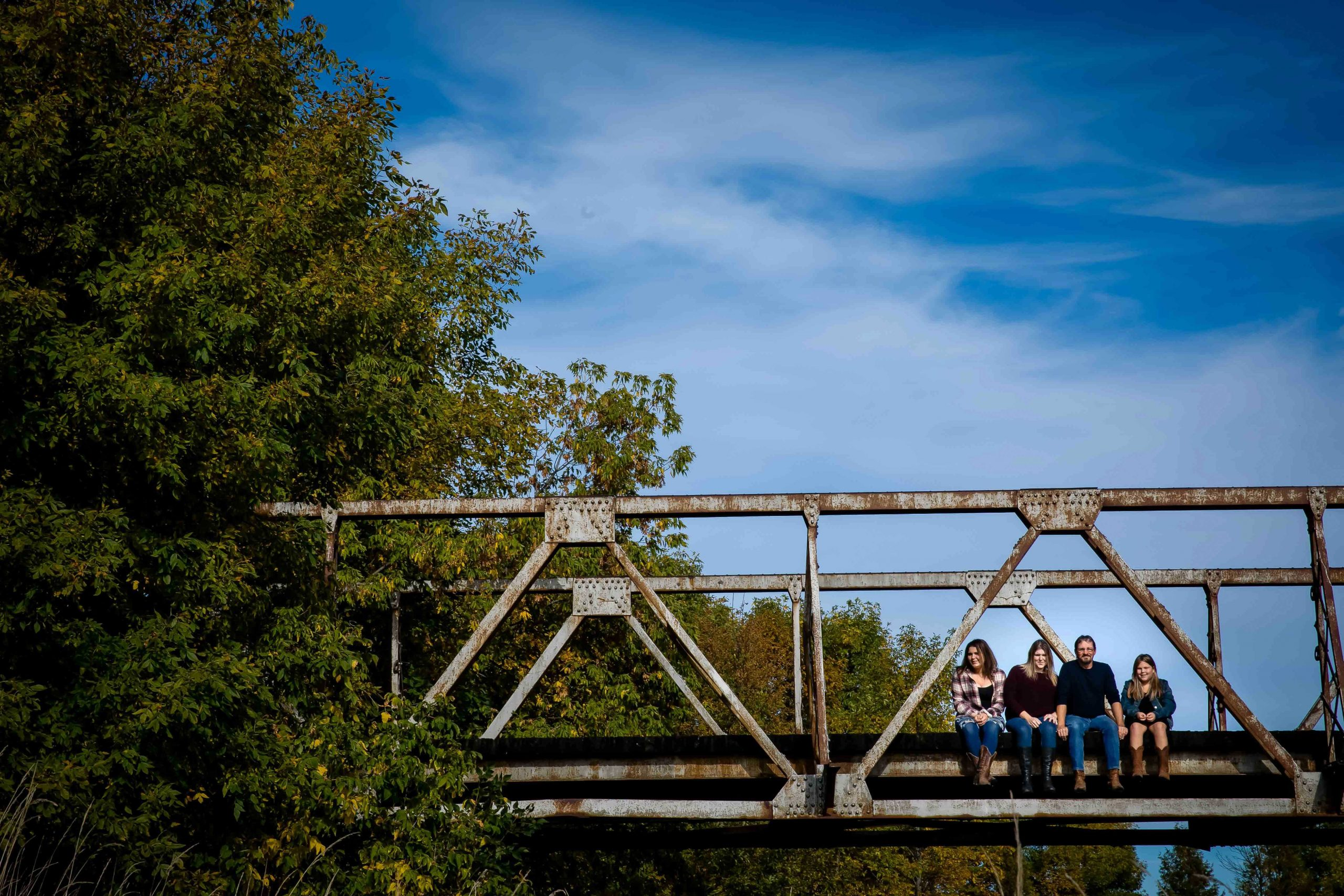 family photo of mother father and two teenage daughters sitting on an old railway bridge