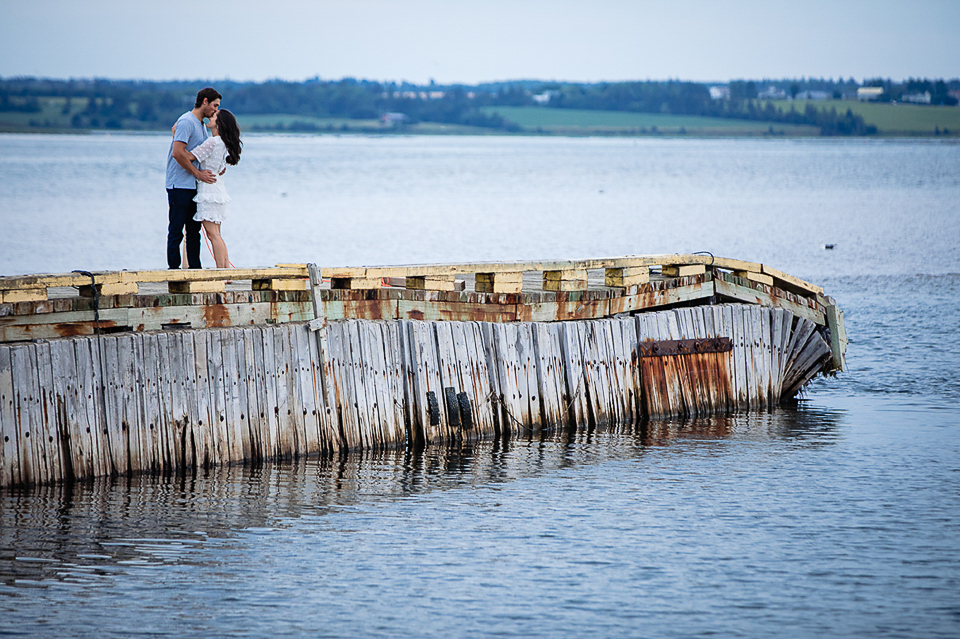 Engaged couple kiss at the end of a pier.