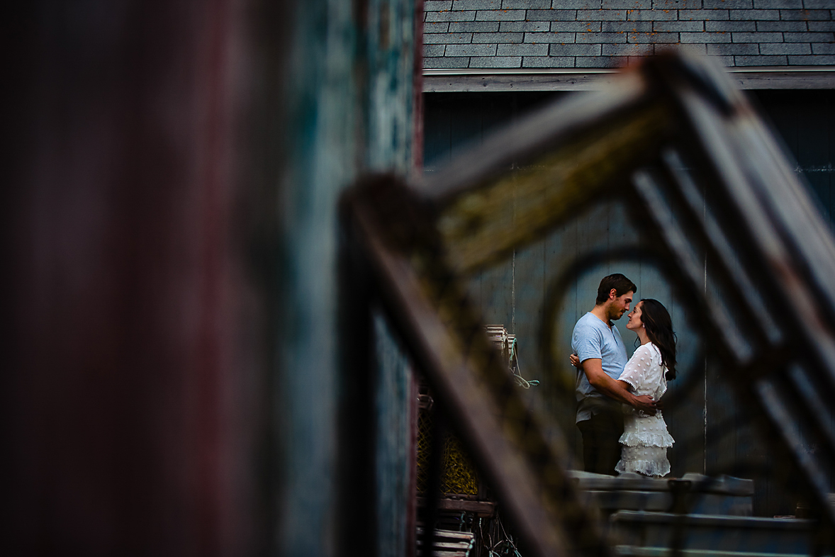 A fishing cage frames an embracing couple.