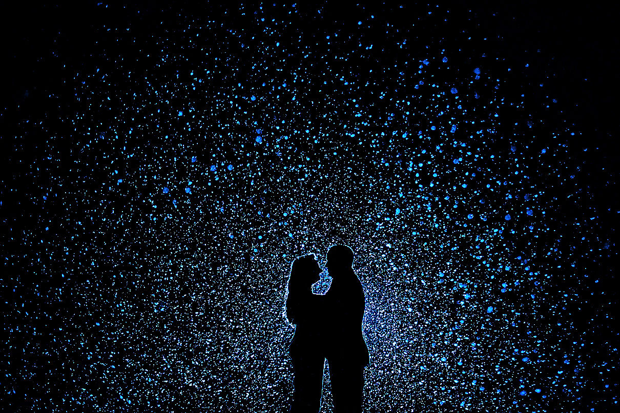 Silhouette of couple in front of a starry backdrop.